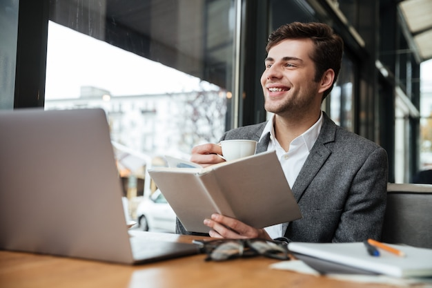 Happy businessman sitting by the table in cafe with laptop computer while reading book and drinking coffee Free Photo