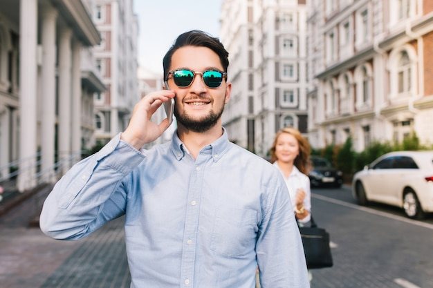 Happy businessman in sunglasses speaking on phone on street. pretty blonde girl catching him from behind Free Photo