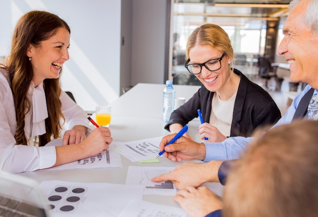 Happy businesspeople discussing a financial plan in the meeting Free Photo