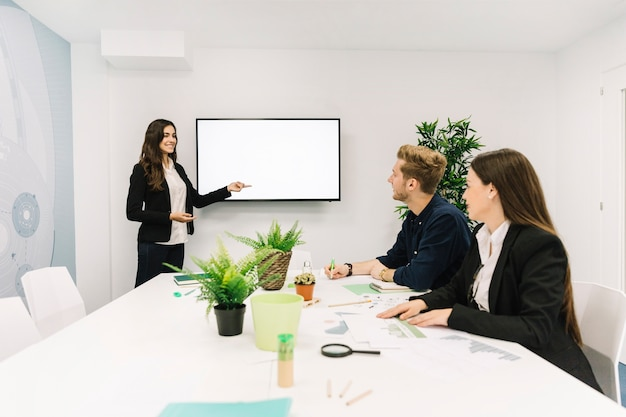Happy businesswoman giving presentation to her partners in business meeting Free Photo