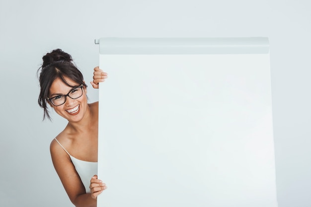 Happy businesswoman hiding behind the whiteboard Free Photo