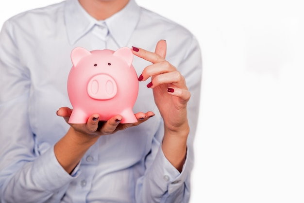 Happy businesswoman holding piggy bank against white background Free Photo