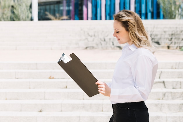 Happy businesswoman looking in folder outdoors Free Photo