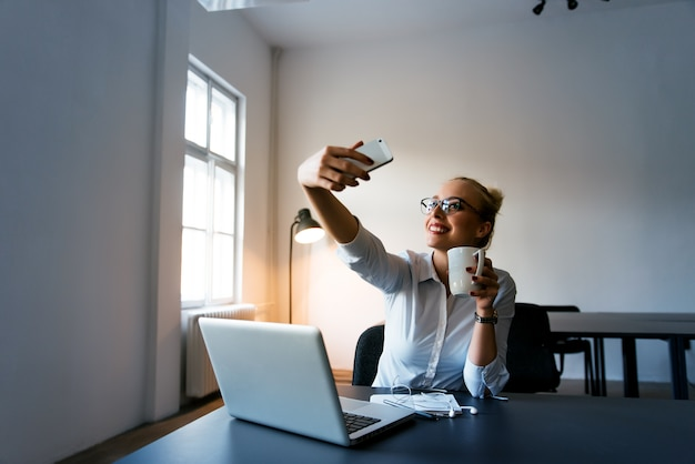 Happy businesswoman making selfie in office with cup of coffee Premium Photo