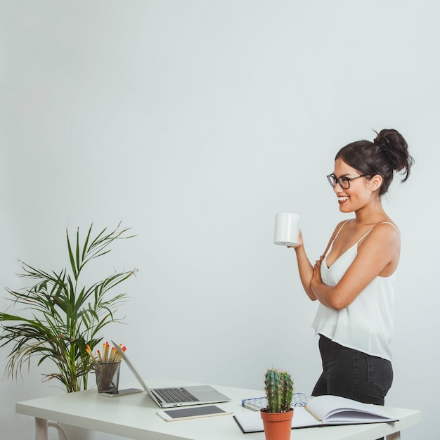Happy businesswoman posing with a coffe mug in the office Free Photo