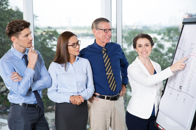 Happy businesswoman presenting chart to colleagues Free Photo