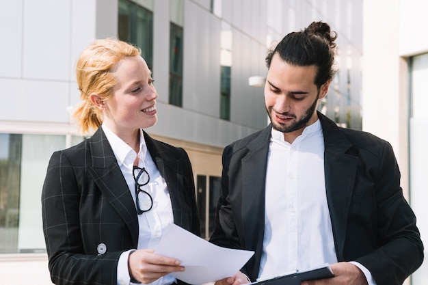 Happy businesswoman showing document to businessman Free Photo