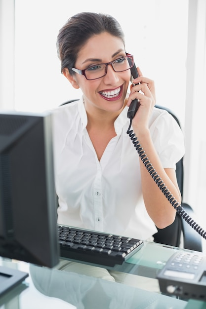 Happy Businesswoman Sitting At Her Desk Talking On The Phone