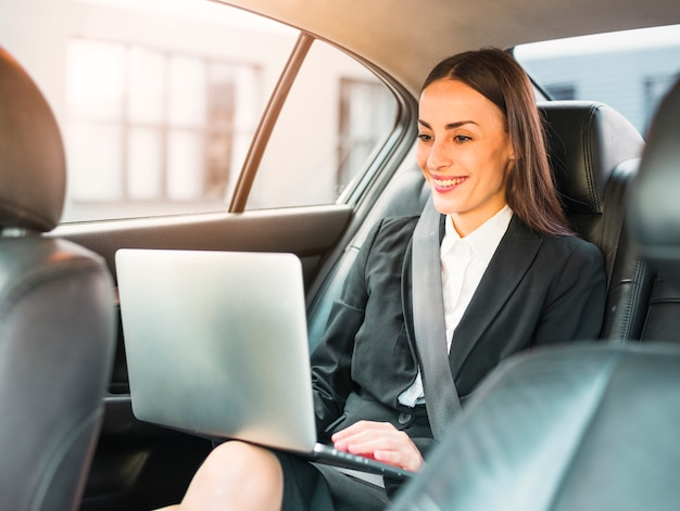 Happy businesswoman traveling by car using laptop Free Photo