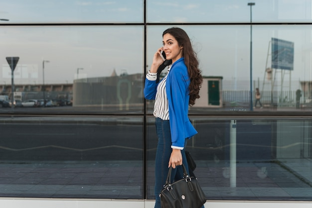 Happy Businesswoman Walking While Talking On The Phone Photo