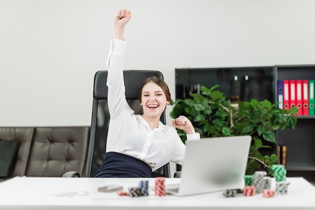Happy businesswoman wins in online casino while playing poker in the office at workplace Premium Photo