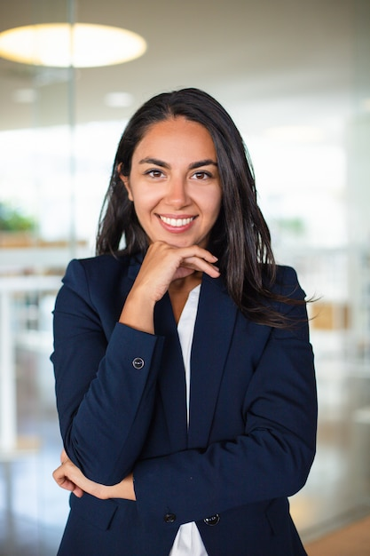 Happy businesswoman with hand on chin Free Photo