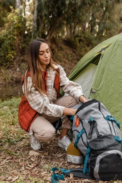 Ragazza di campeggio felice nell'imballaggio della foresta Foto Gratuite