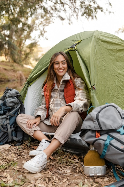Happy camping girl in the forest sitting in the tent Free Photo