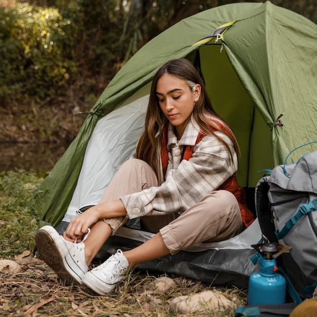 Ragazza di campeggio felice nella foresta che lega i suoi lacci Foto Gratuite