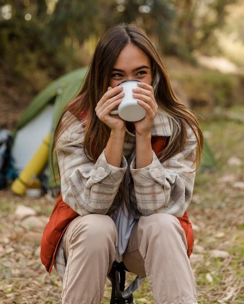 Счастливая девушка кемпинга в лесу, пить из кружки Бесплатные Фотографии