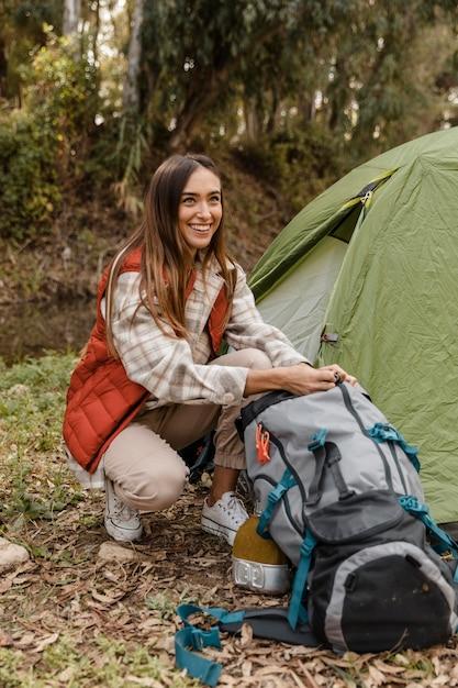 Счастливая девушка в кемпинге в лесу ищет рюкзак Бесплатные Фотографии