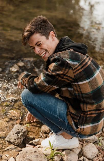 Uomo di campeggio felice nella foresta che si siede sulla riva del fiume Foto Gratuite