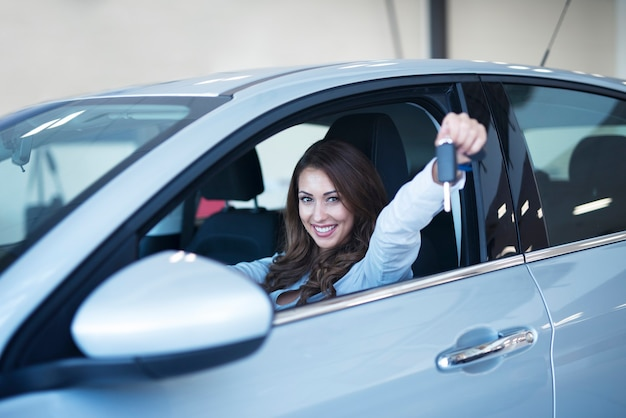 ディーラーのショールームで鍵を見せて新しい車に座っている幸せな車のバイヤー 無料写真