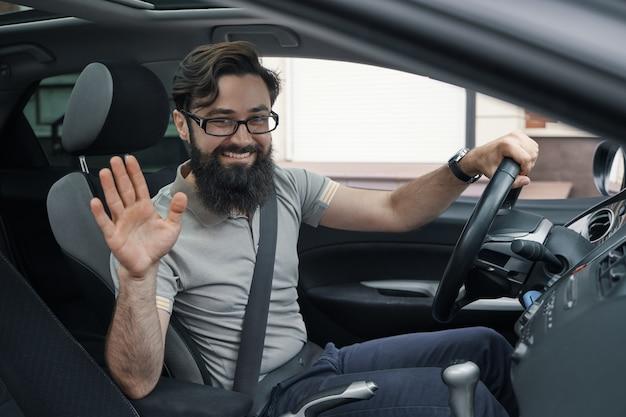 Felice automobilista con cintura allacciata agitando Foto Gratuite