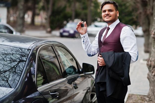 Счастливый владелец автомобиля с ключами под рукой. стильный индийский бизнесмен в формальных износа стоял против черный бизнес автомобиль на улице города. Premium Фотографии