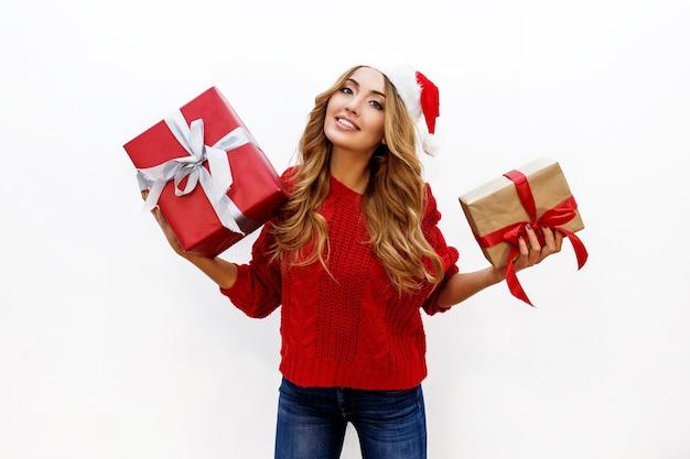 Счастливая беззаботная белокурая женщина празднует новогоднюю вечеринку с подарками. в красной шапке санты и вязаном свитере. позирует Бесплатные Фотографии