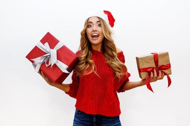 Donna bionda spensierata felice che celebra i regali della holding della festa di capodanno. indossa il cappello rosso della santa e il maglione lavorato a maglia. in posa Foto Gratuite