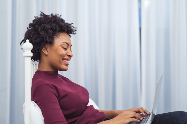 Happy casual beautiful american african woman working on laptop computer while setting  on the bed in the house. Premium Photo