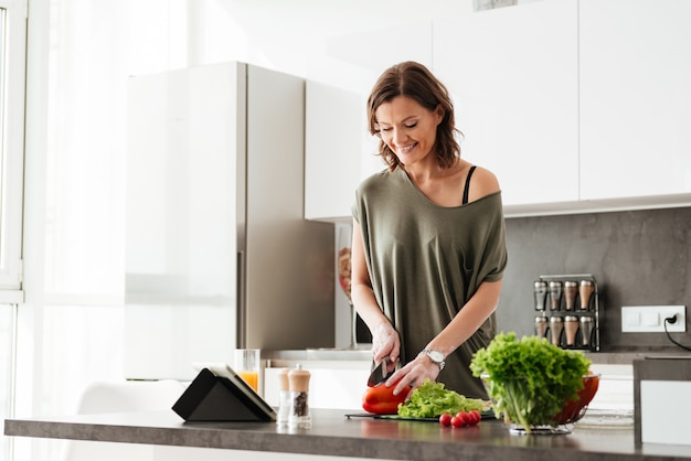 Happy casual woman cutting vegetables Free Photo