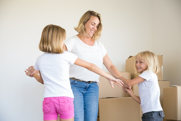 Счастливая кавказская блондинка мама и две девочки танцуют в комнате среди картонных коробок Бесплатные Фотографии