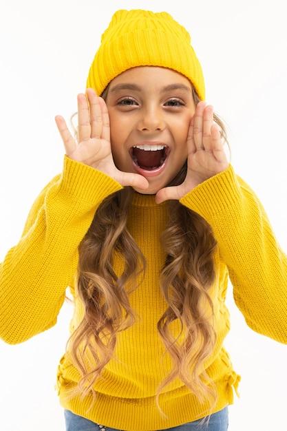 黄色い帽子とフーディ孤立の幸せな白人の女の子 Premium写真