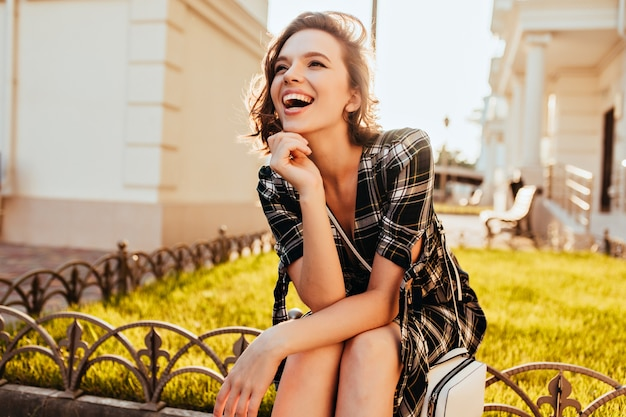 Happy caucasian girl looking in distance while posing in park. refined short-haired woman in checkered attire enjoying sunny autumn morning. Free Photo