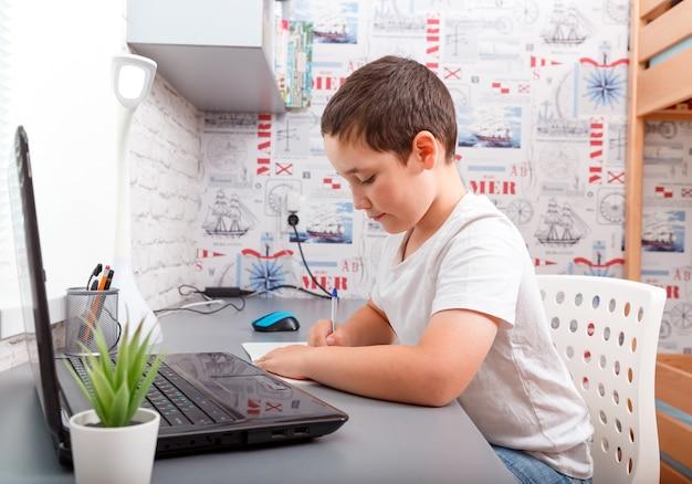 宿題を机に座って幸せな白人少年 Premium写真