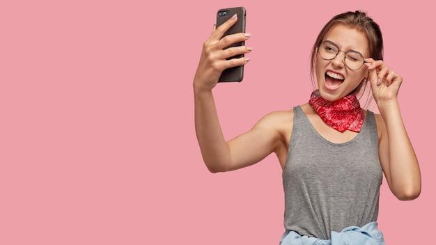幸せな白人女性が目を瞬き、現代のスマートフォンで自分撮りのポーズをとる 無料写真