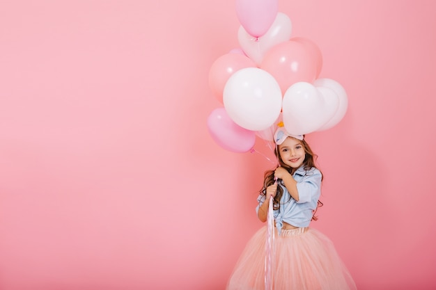 Happy celebration of birthday party with flying balloons of charming cute little girl in tulle skirt smiling to camera isolated on pink background. charming smile, expressing happiness. place for text Free Photo