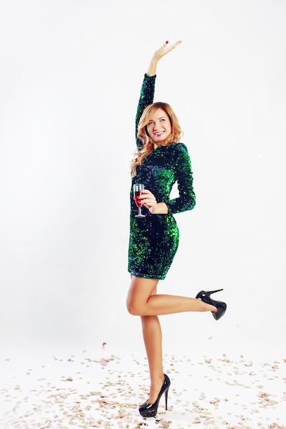 パーティーを楽しんで、ワインを飲みながら緑のスパンコールのドレスで幸せなお祝い女。金色の紙吹雪。 無料写真