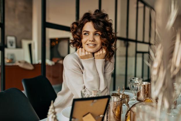 クリスマスを待っている幸せな感情で笑顔の巻き毛の髪型を持つ幸せな魅力的な女の子 無料写真