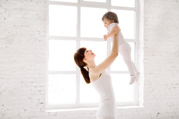 귀여운 작은 여자 아기를 들고 흰 마모에 행복 매력적인 스포티 한 어머니 오버 헤드 프리미엄 사진