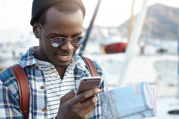 Felice e allegro uomo afroamericano che viaggia da solo in una località turistica europea con la mappa cartacea, guardando eccitato alla ricerca di ristoranti o ostelli nelle vicinanze usando il suo smartphone, vestito casualmente Foto Gratuite