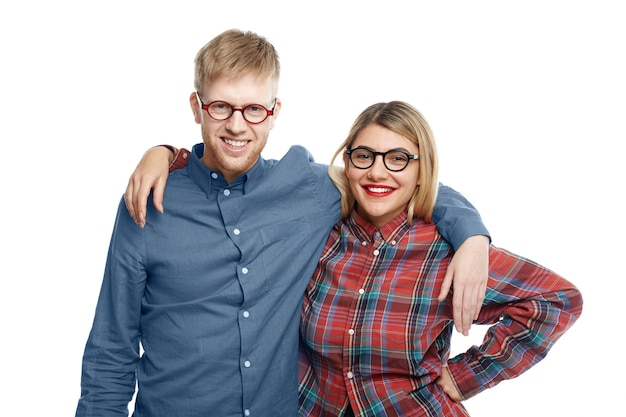 Happy cheerful best friends male and female wearing stylish oval eyewear embracing and smiling broadly while posing for picture after long separation, glad to finally see each other Free Photo