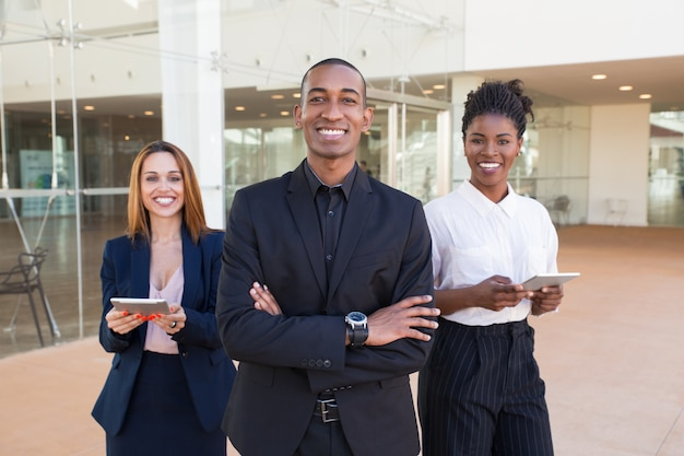 Happy cheerful business people posing in office hallway Free Photo