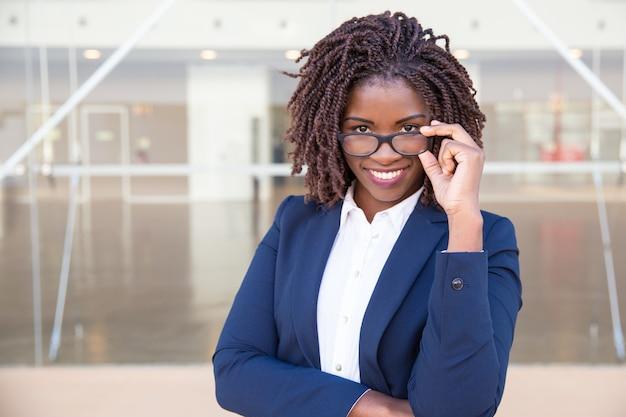 Happy cheerful female office employee touching eyewear outside Free Photo