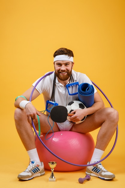 Happy cheerful fitness man sitting on a sports ball Free Photo