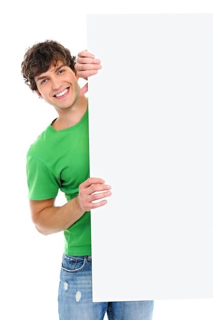 Il ragazzo allegro felice osserva fuori dal tabellone per le affissioni in bianco su bianco Foto Gratuite