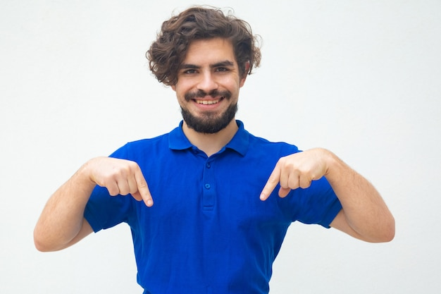 Happy cheerful guy pointing fingers down Free Photo