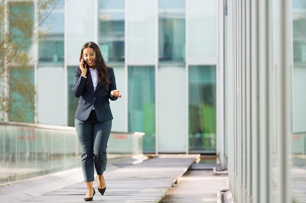 Happy cheerful latin businesswoman talking on phone Free Photo