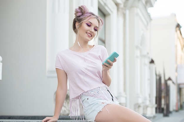 Happy cheerful young blonde with pink hair sitting in the street, taking a picture of herself with a mobile phone. ginger student girl resting on the street after college. Premium Photo