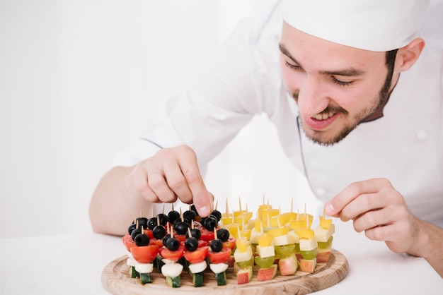 Happy chef arranging snacks on wooden board Free Photo