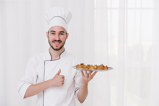 Happy chef holding plate with flamed meringue Free Photo