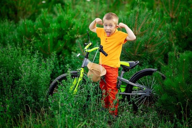 Счастливый ребенок мальчик в оранжевой одежде с велосипедом дурачится в зеленой траве летом Premium Фотографии